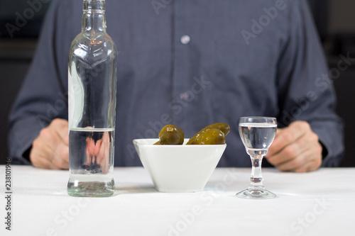 Butelka wódki, ogórki kiszone, kieliszek z wódką stoją na stole przykrytym białym obrusem. W tle postać mężczyzny siedzącego za stołem.