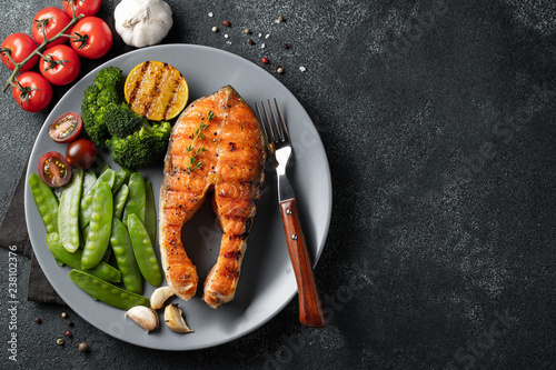 Photo  Tasty and healthy salmon steak with green peas, broccoli and tomatoes on a gray plate