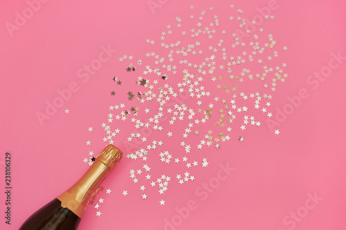 Champagne bottle with confetti stars on pink background. Copy space, top view - 238106329