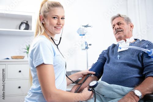 junge hübsche Krankenschwester pflegt einen pazienten, misst blutdruck, blutzuck Canvas Print