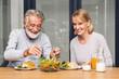Leinwandbild Motiv Senior couple enjoy eating  healthy breakfast together in the kitchen.Retirement couple concept
