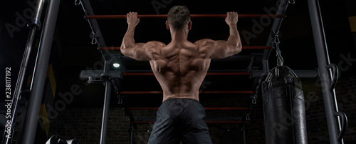 Muscular man working out in gym doing exercises, strong male naked torso abs Wallpaper Mural