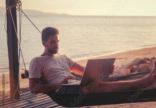 Fotografia Young attractive guy a man with a beard in a hammock with a laptop on the backgr