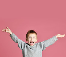 Young Boy Kid Jumping In Grey Hoodie With Hands Spread Up Laughing Smiling On Pink