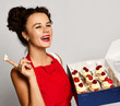 Young woman chef cook hold sweet cup cakes box with cream happy surprised on gray