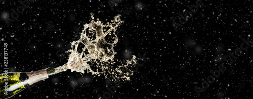 Celebration theme with splashing champagne on black background with snow and free space. Christmas or New Year, Valentines day background.