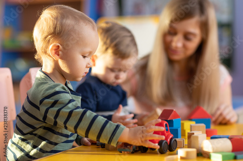 Preschool teacher and cute kids boys playing in kindergarten