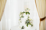 White wedding cake with flowers.  The word Love with heart.