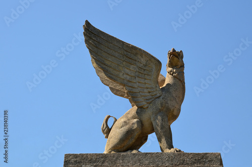 The stone griffin sits on a pedestal against the blue sky in the sunlight. Bottom view.