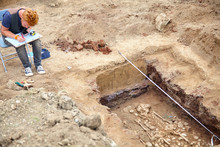 Archaeological Excavations. Young Stylish Archaeologist Drows Of Human Bones, Skeleton And Skull In The Ground Tomb. Real Digger Process. Earphones, Mobile Phone, Sunglass, Tools. Outdoors, Copy Space