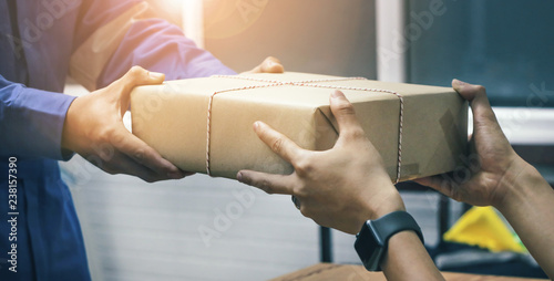 Young woman hand appending signature in report paper after receiving parcel from courier at home Canvas Print