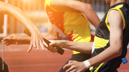 Professional Athlete passing a baton to the partner against race on racetrack Fototapeta