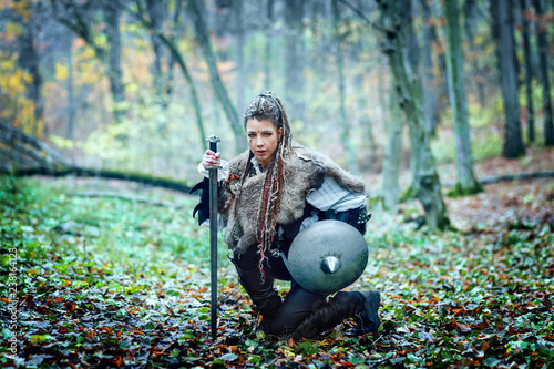 Photo  Portrait of dangerous, beautiful scandinavian viking woman warrior fur collar and specific makeup holding ax and shield, ready to attack and defend her territory