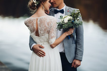 Back View Of Husband Embracing His Beautiful Elegant Wife In Lace Wedding Dress With Lovely Bouquet Against Unfocused Lake Surface.