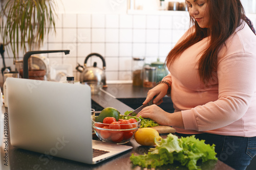 Cadres-photo bureau Cuisine Overweight woman using laptop to watch video recipe while making vegan vitamin avocado salad, slicing leaf lettuce on wooden cutting board. Healthy food, weight loss, dieting and nutrition concept