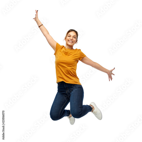 Fotografia motion, freedom and people concept - happy young woman or teenage girl jumping o
