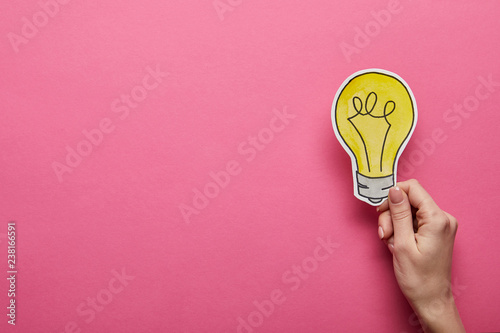 Fotomural  top view of hand holding yellow light bulb on pink background