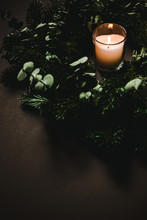 Burning Candle Near Conifer Branches And Cone