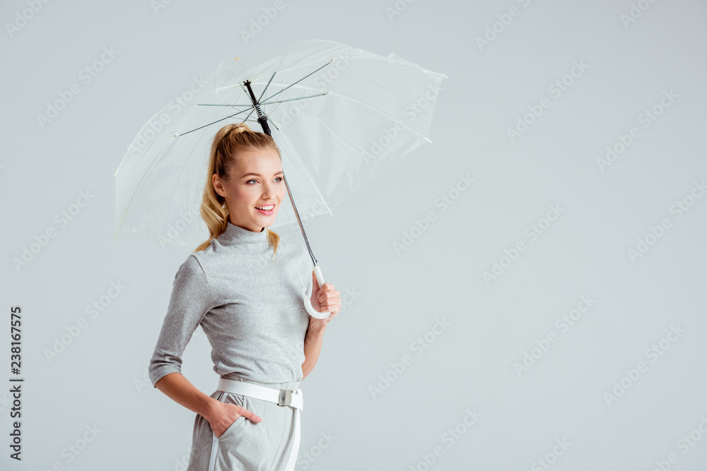 Fototapety, obrazy: beautiful woman in grey clothes and hand in pocket posing with transparent umbrella isolated on grey