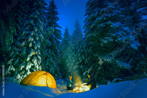 Obraz couple camping with campfire and tent outdoors in winter - fototapety do salonu