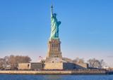 Fototapeta New York - Vista desde el rio Hudson, al atardecer, de la estatua de la libertad y su isla, donde numerosos turistas, van a visitarla cada dia,desde Manhattan.