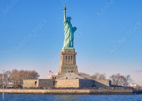 Photo  Vista desde el rio Hudson, al atardecer, de la estatua de la libertad y su isla, donde numerosos turistas, van a visitarla cada dia,desde Manhattan