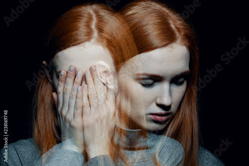 Obraz na plátně Porter of beautiful redhead girl with psychotic disorders covering her face, hid