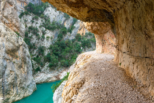 A path excavated in the rock allows to cross Congost de Mont-Rebei defile, border between Catalonia and Aragon, Spain