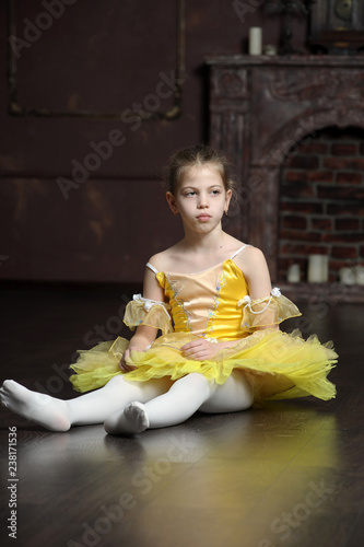 Fotografía  brunette girl in a yellow ballet dress sitting