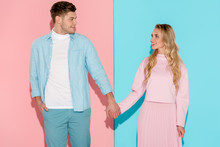 Happy Couple Holding Hands And Looking At Each Other On Pink And Blue Background