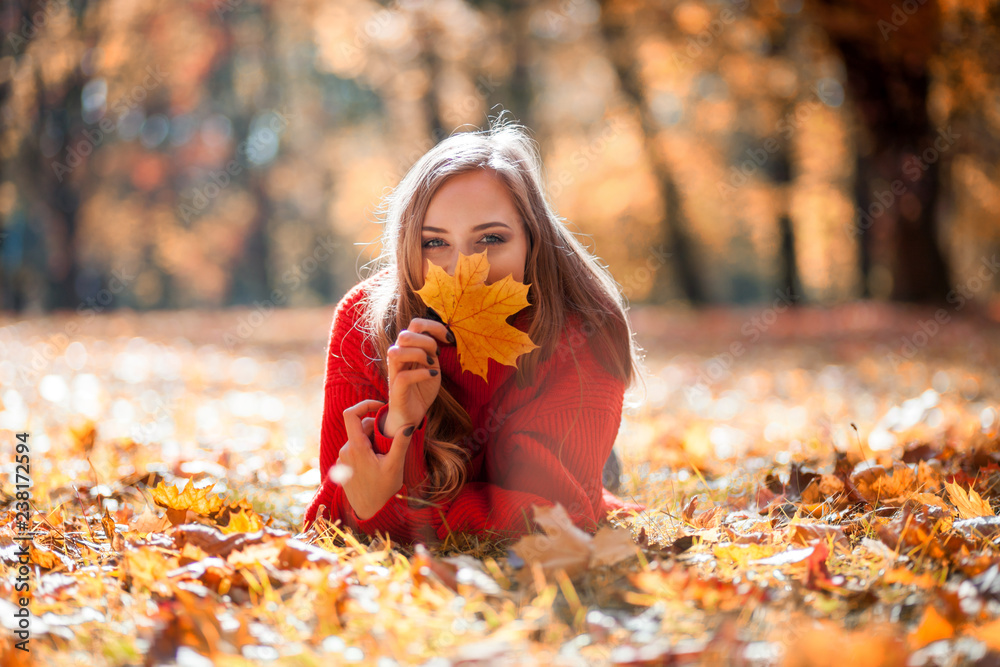 Fototapety, obrazy: Natural woman holding colorful autumn leaf lying on lawn in the park
