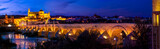 Panorama of ancient stone Roman bridge illuminated in night time with glowing Moorish Mosque Cathedral (Mezquita) on background in Cordoba, Spain