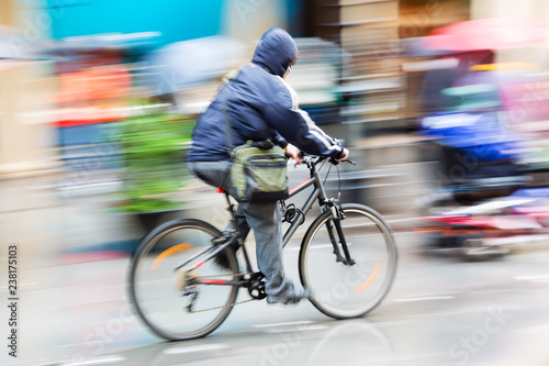 person with rain cape riding a bicycle