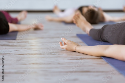 Group of people in yoga class meditating in Shavasana pose. Healthy lifestyle and wellness, recreation concept in fitness studio or gym