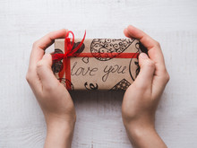 Hands Holding A Box With A Gift, Tied By A Ribbon, On A White, Isolated Surface. Top View, Close-up. Preparing For The Holidays. Happy Family Concept