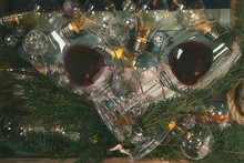 Two Glasses Of Red Wine And Retro Christmas Garland With Lighted Lamps Over White Marble Background. Flat Lay, Space
