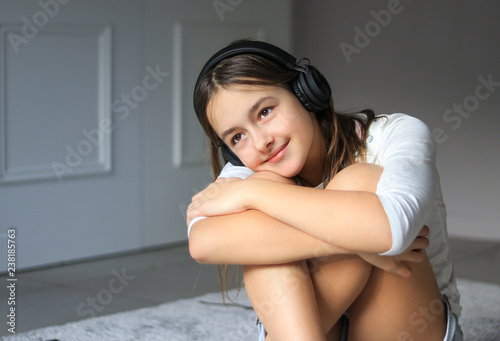 Beautiful happy romantic smiling preteen girl with wireless headphones listening to music sitting on floor at home hugging her khees relaxing. Calm leisure time