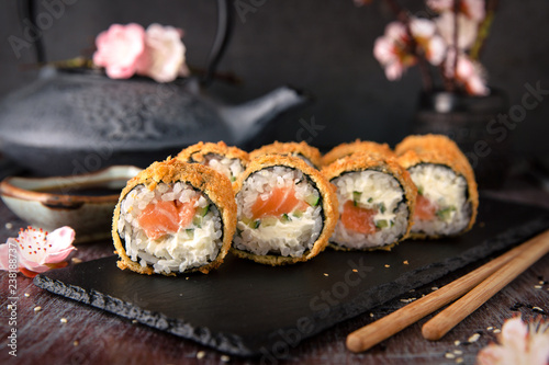 Fototapeta Hot fried Sushi Roll with salmon, avocado and cheese. Sushi menu. Japanese food. obraz