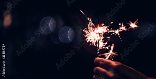Photo  Hand holding burning Sparkler blast on a black bokeh background at night,holiday celebration event party,dark vintage tone