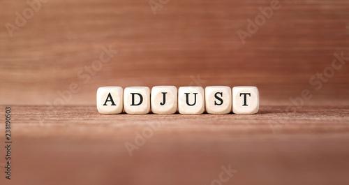 Fotomural Word ADJUST made with wood building blocks