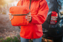 Picture Of Orange Firt Aid Kit Bag Young Oman Hold With Both Hands. She Stads At Tent. Model Wears Orange Jacket.