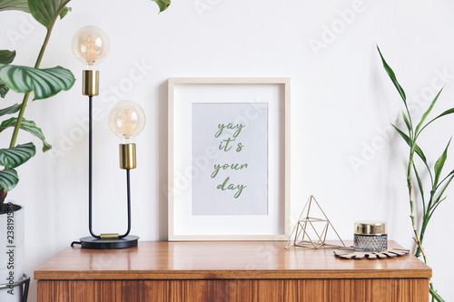 Fototapeta Retro and minimalistic white interior with mock up photo frame on the vintage brown shelf,tropical plant in cement pot, table lamp, gold pyramid and accessories. obraz