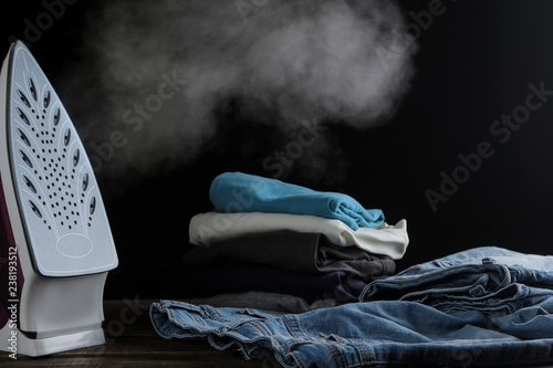 lilac iron releases steam and a stack of clothes on a black background Fototapeta