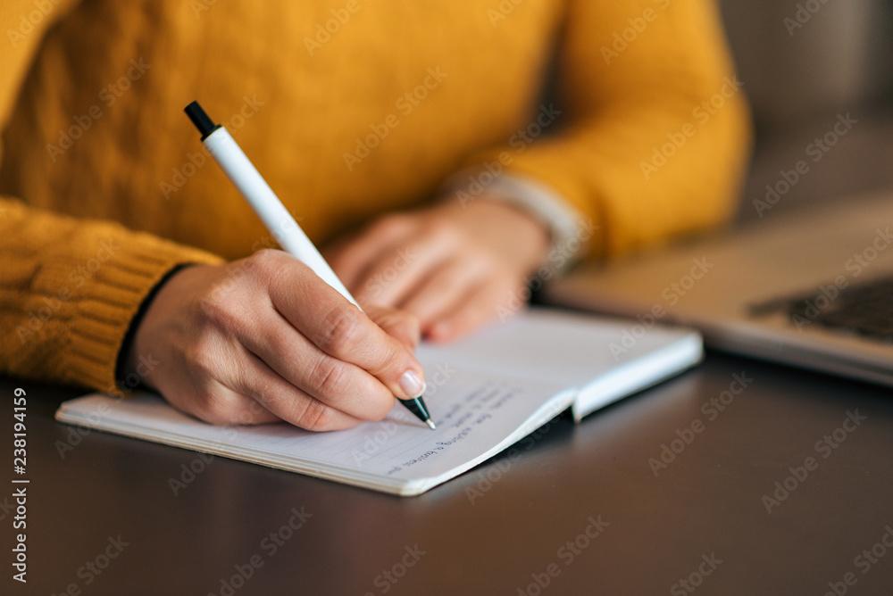 Fototapeta Writing in notebook. Close-up.
