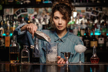 Female Bartender Adding To The Measuring Glass Cup An Ice Cubes With Shovel