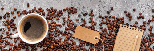 close-up-coffee-beans-coffee-cup-and-lined-paper-notebook-on-stone-table-top-view-panoramic-flat-lay