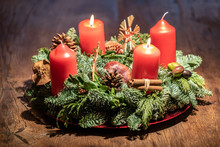 Advent Wreath And Two Burning Red Candles On A Wooden Table Studio