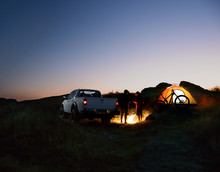 Friends Near Bonfire, Pickup Truck, Tent And Bike At Night Camp In The Mountains. Adventure And Travel Concept