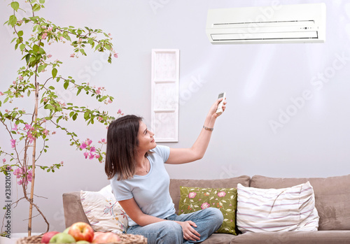 woman using remote control   of  aircondition