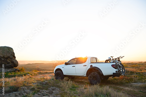 Obraz Pickup Offroad Truck with Bikes in the Body in the Mountains at Sunset. Adventure and Car Travel Concept. - fototapety do salonu